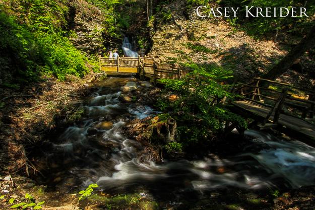 Pond Run Creek loops under a footbridge at Bridesmaid's Falls on a sunny day at Bushkill Falls, June 9, 2013.