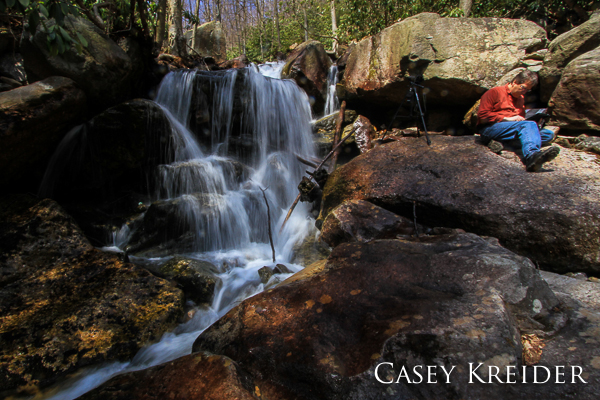 A photographer studies his work on a tablet next to a waterfall on Glen Onoko Run in Lehigh Gorge State Park.