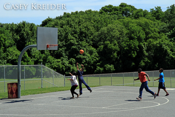 Kids play basketball after police removed a stolen car involved in a police pursuit and foot chase from the other end of the court along South Ann Street in Lancaster Friday morning.