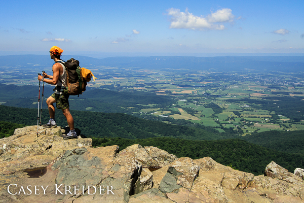 A hiker poses atop Stony Man Mountain over the Shenandoah Valley in Shenandoah National Park. Massanutten Mountain forms the horizon in the distance.
