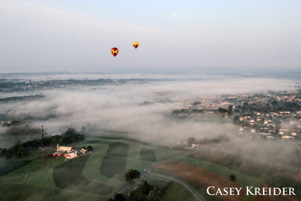 Two hot air balloons with the United States Hot Air Balloon Team coast above a layer of morning fog over East and West Lampeter townships Friday, July 3, 2015.