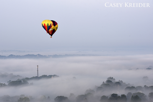 Fog lifts over Lancaster County as two hot air balloons from the United States Hot Air Balloon Team coast through the morning sky Friday.